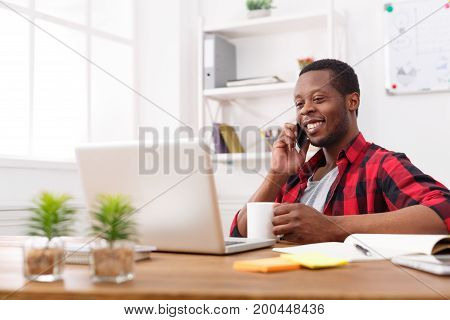 Business call. Young african-american businessman in casual has mobile phone talk in modern white office interior.