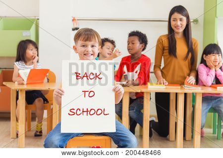 Cute boy holding back to school poster with happy face in kindergarten classroom kindergarten education concept Vintage effect style pictures.