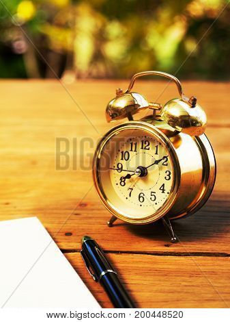 Soft focus of blank notebook with vintage alarm clock and black pen on wood table. The background is green from tree and light bokeh