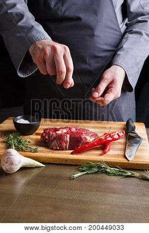 Man sprinkles rib eye steak with pepper salt. Chef working at open restaurant kitchen. Fresh meat, garlic, rosemary and red chilli on wooden board. Modern restaurant cuisine backgroung, copy space