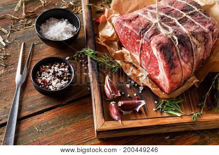 Raw black angus beef bound with rope in craft paper on cutting board. Aged prime marble meat, herbs, spices and meat fork at rustic wood background, closeup