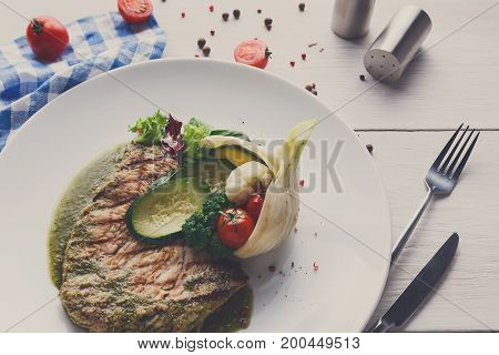 Dining at restaurant. Grilled black angus steak with vegetables in fennel and green bell pepper sauce. Healthy food, served on round plate at white wood background and checkered cloth, copy space