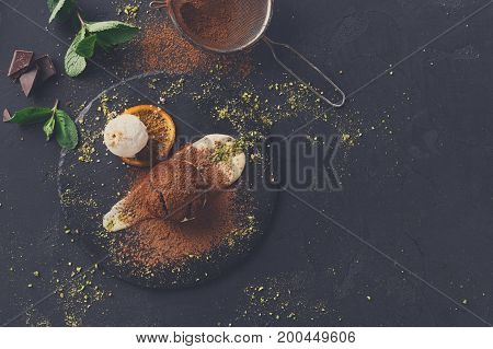 Exquisite french dessert. Chocolate fondant with creme anglaise and vanilla ice cream on round slate with pistachio crumble. Black background with cocoa, mint and sieve, top view, copy space