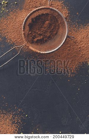 Sweet background. Cocoa powder in a sieve and sprinkled on surface, chocolate pieces on black slate. Top view, copy space