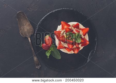 Fitness restaurant dessert at black background. Anna Pavlova meringue with low-fat whipped cream and fresh strawberry on slate and cake spatula aside, top view, copy space