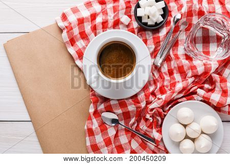 Morning coffee at restaurant. White porcelain cup of black bitter coffee with treats on stylish checkered tablecloth and craft paper on wooden background, top view, copy space