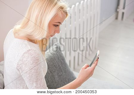 Portrait of happy young woman with mobile phone sitting on couch at home.