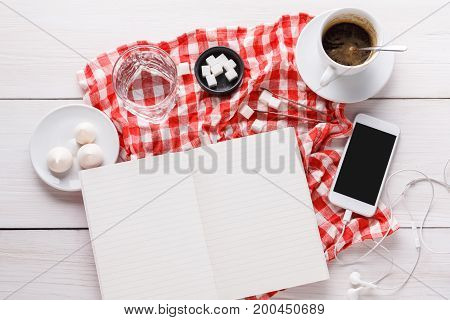 Coffee break at office. Porcelain cup of black coffee, lump sugar, blank notebook and smartphone with earphones on checkered tablecloth at white wooden background, top view, copy space