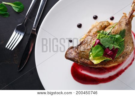 Exclusive restaurant meals. Duck confit with braised cabbage, baked apple and cranberry sauce served on snow white plate with cutlery on black table background, copy space, top view