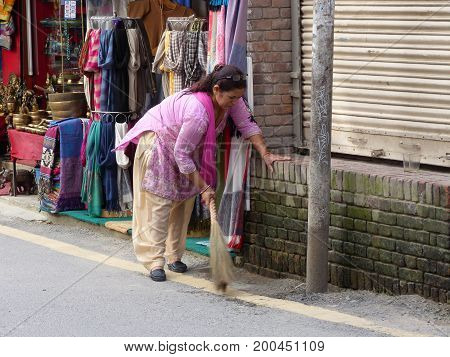 Kathmandu, Nepal, september 4, 2015: Rush in streets of Thamel, the tourist place in Kathmandu, Nepalese woman sweeping in front of her shop