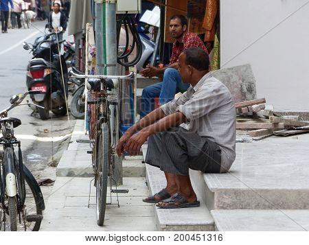 Kathmandu, Nepal, september 4, 2015: Rush in streets of Thamel, the tourist place in Kathmandu, Nepalese men sitting on the path and relaxing