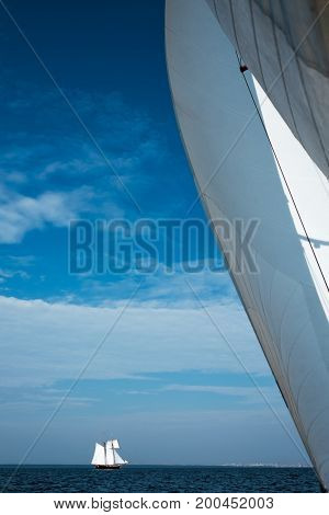White sail yacht against the blue sky and the sea. Small boat at distance