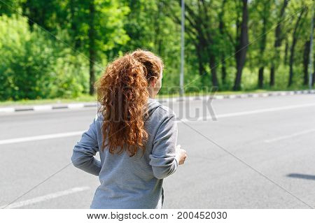 Young sporty woman running in green park during morning workout, copy space, back view