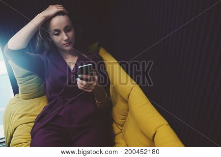 Tired beautiful caucasian businesswoman with headache is laying on fenced sofa in office chillout zone holding her head with hand and having online conversation with her colleagues via smartphone