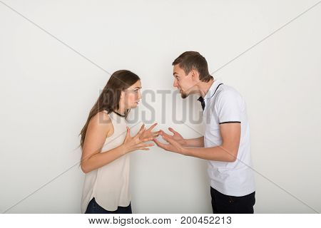Relationship problems. Young couple arguing, yelling on each other because of disagreements, white background