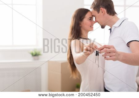 Key of new home. Happy young couple standing close to each other and smiling while holding keys from house, copy space