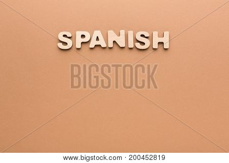 Word Spanish on beige background. Foreign language learning, education concept