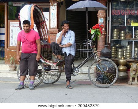 Kathmandu, Nepal, september 4, 2015: Rush in streets of Thamel, the tourist place in Kathmandu, Two nepalese men wait for customers