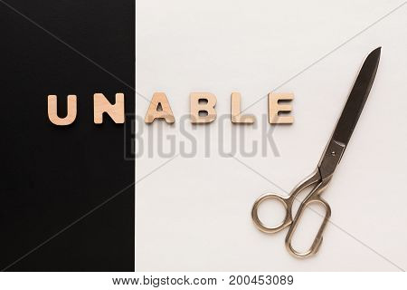 Positive motivation concept. Changing word unable into able with scissors