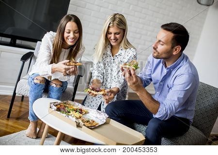 Young Friends Eating Pizza In The Room
