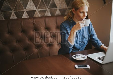 Young Woman Sitting In Cafe, Drinking Coffee And Surf The Internet With A Smile