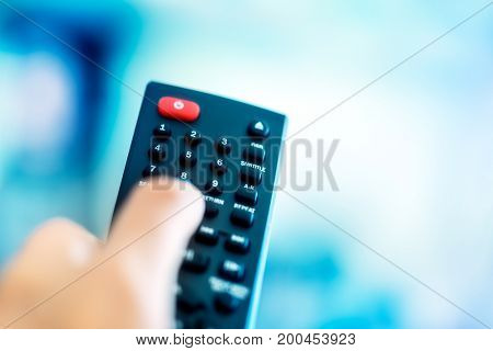 TV remote, man holding in hand remote control and choosing tv canal, using smart device to look video