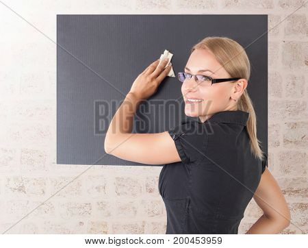 Portrait of a beautiful young teacher writing on blackboard, working in the university, good education, back to school concept