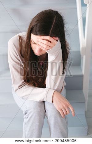A woman sitting alone and depressed at home
