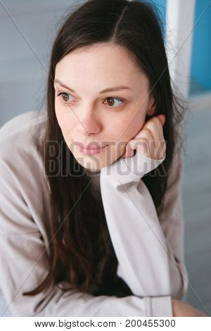 thinking young woman is sitting at home.