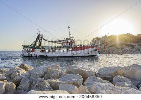 MAKARSKA RIVIERA, CROATIA - 10 JULY, 2017: Pleasure boat with cheerful tourists enters the port of Makarska, Croatia.