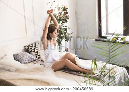 Good Morning. Young Beautiful Woman Yawns And Pulls His Hands Up While Sitting On The Bed