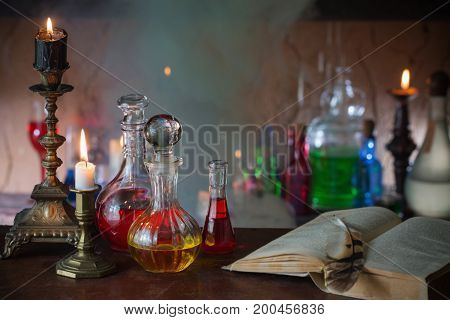 Magic potion ancient books and candles on dark background