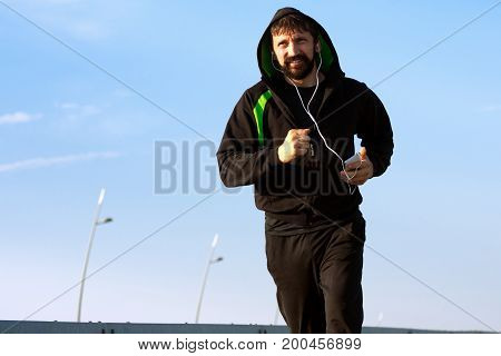 The jogging running man is listening music with earphones from mobile phone.