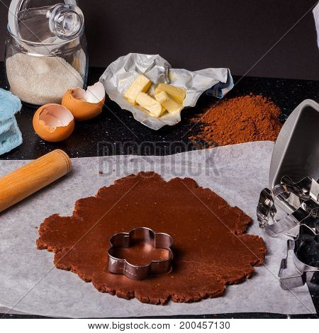 The process of baking chocolate cake base of shortcrust pastry. Working with dough at home kitchen. Ingredients for baking: eggs, flour, butter, sugar on black table and dark background.
