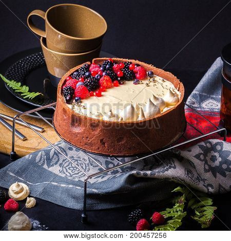 Cake with white chocolate mousse, lime confit, fruits and berries on top as decoration. The process of preparing a tea party with homemade fresh cake.
