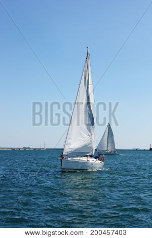 white sailing boat on  waves of black sea