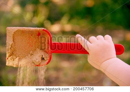 Red Plastic Scoop Scoop In A Children's Hand. Play In The Sandbox. With A Scoop Of Sand Falls. Symbo