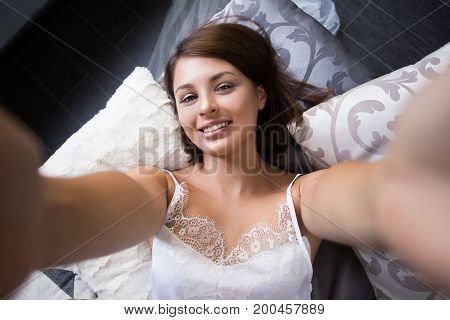 Beautiful Cheerful Girl In Bed Does Selfie. Top View Of Attractive Young Woman Smiling While Lying O