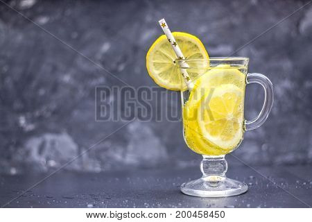 Homemade Lemonade In A Glass With A Handle On A Gray Concrete Background. Water With Slices Of Lemon