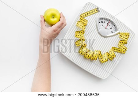 Bathroom scale and measuring tape on white background, top view.