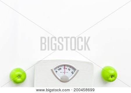 Bathroom scale and green apples on white background, top view.