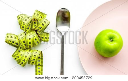 Slimming diet. Apple on a plate on white background, top view.