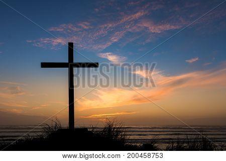 Black cross on a beach with a dusk sky sunset behind it.