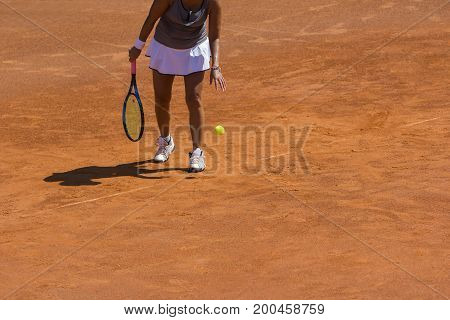 A woman tennis player preparing to serve in tennis cort