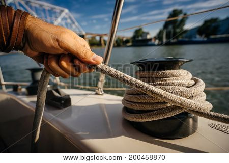 The man's hand holds the end of the rope wound on the small windlass of the yacht ship.
