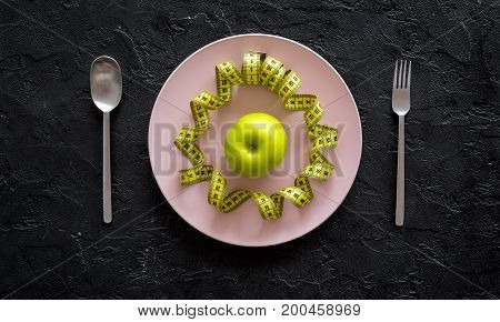 Slimming diet. Apple at plate and measuring tape on black background top view.