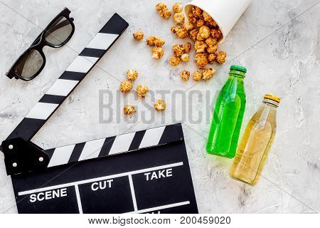 Food for watching film. Popcorn and soda near clapperboard, glasses on grey background top view.