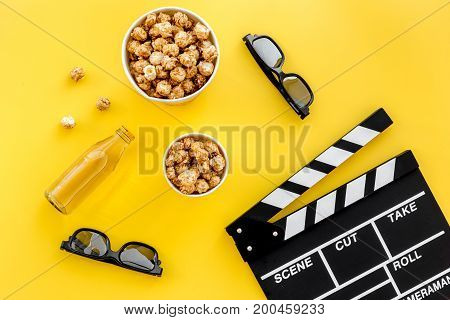 Snacks for film watching. Popcorn and soda near clapperboard, glasses on yellow background top view.