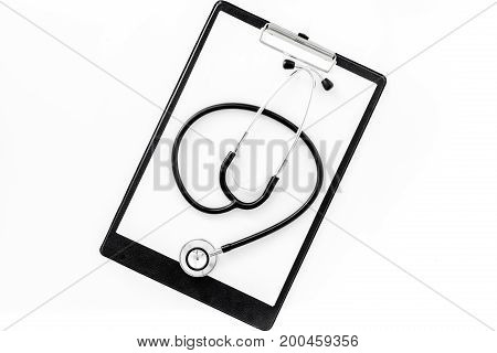 Doctor's table. Clipboard and stethoscope on white background, top view.