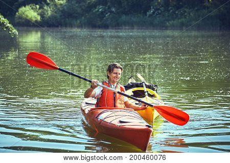 Man paddling in a kayak on river.